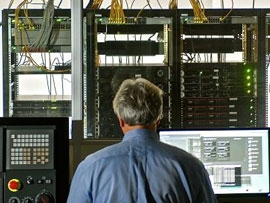 Back of Andrew Dugenske in front of FIS lab equipment